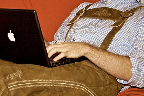 Mann in Lederhosen mit Laptop auf dem Schoß